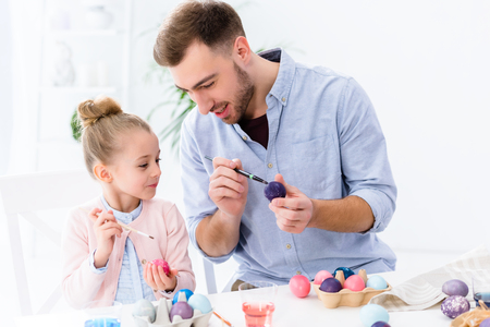 Child and father coloring eggs for Easter