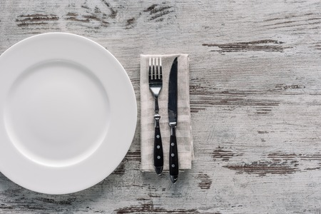 white plate and fork with knife on napkin on wooden table Фото со стока