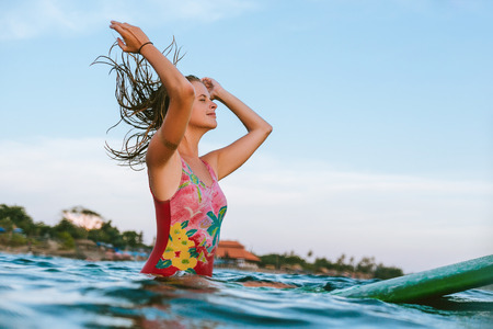 young woman readjusting wet hair while sitting on surfing board in ocean