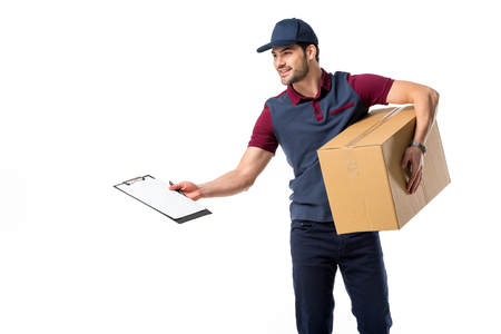 smiling delivery man with cardboard box, empty notepad and pen isolated on white