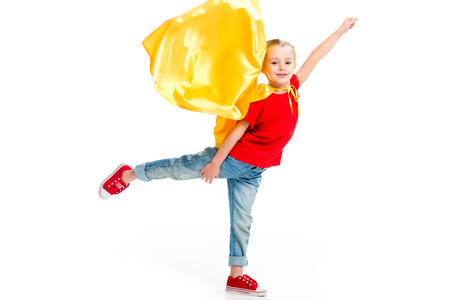 Little smiling supergirl in yellow cape standing on one leg and gesturing by hand isolated on white Stock Photo
