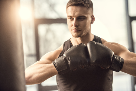 handsome muscular young sportsman in boxing gloves looking away while training in gym Archivio Fotografico - 111599277