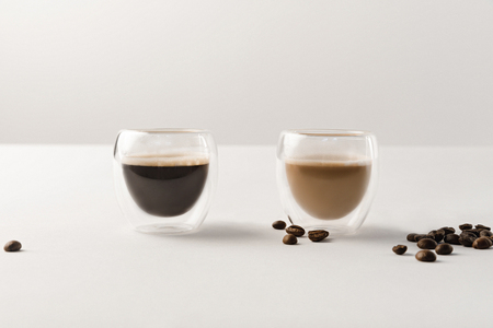 Two cups with coffee on white background with coffee beans Stock Photo