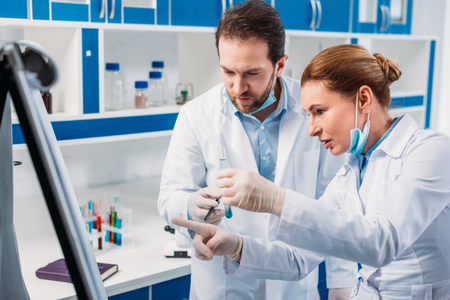 scientist in white coats near board for notes having discussion during work in lab Standard-Bild