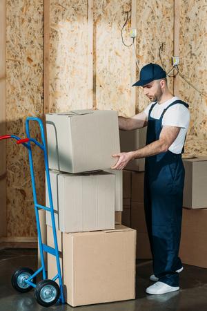 Loader man stacking cardboard boxes on cart