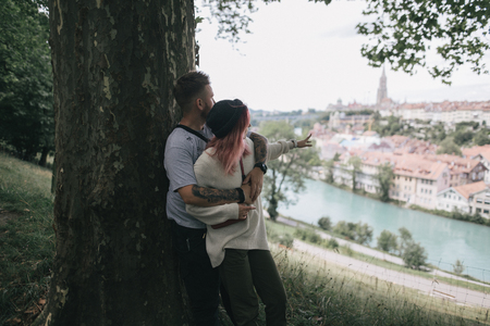 young couple in love hugging near big tree and looking at Bern cityscape Stock Photo