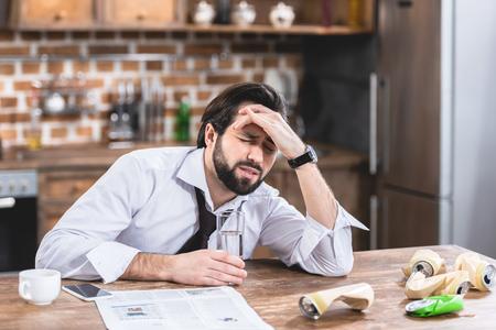 eenzame zakenman met hoofdpijn en kater in de keuken