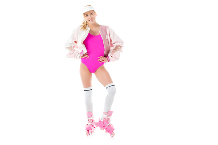Girl dressed in pink having fun on roller skates isolated on white