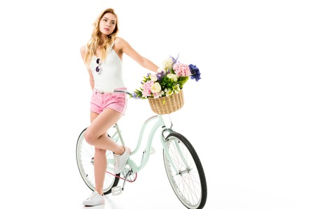 Young girl standing by cruiser bicycle with flowers in basket isolated on white 스톡 콘텐츠