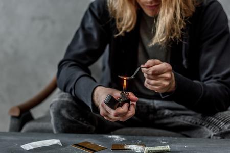 Captura recortada de adicto drogadicto hirviendo heroína en una cuchara con encendedor Foto de archivo