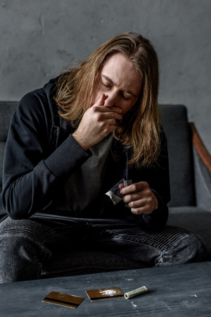 addicted man sniffing cocaine while sitting on couch Stock Photo