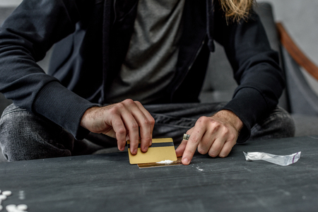 cropped shot of addicted man preparing to take cocaine Stock Photo