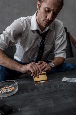 businessman with drug addiction preparing to take cocaine Stock Photo