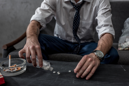 businessman with drug addiction pouring pills on table from bottle