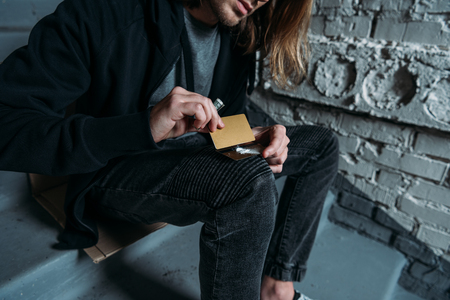 cropped shot of addicted man sniffing cocaine from credit card Stock Photo