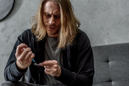 close-up shot of addicted junkie boiling heroin in spoon with lighter
