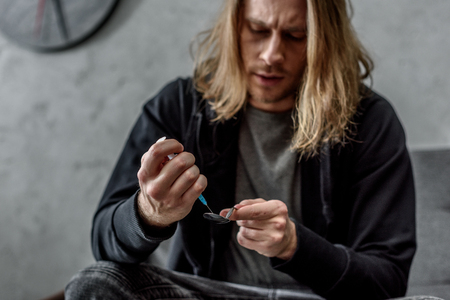 addicted junkie boiling heroin in spoon with lighter