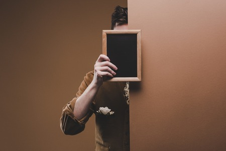 Man in stylish clothes holding empty frame isolated on brown 스톡 콘텐츠