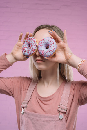 young woman covering eyes with doughnuts in front of pink brick wall Stock Photo