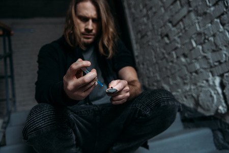 addicted junkie filling syringe with heroin from spoon Archivio Fotografico - 111600654