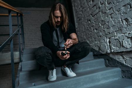 Adicto adicto a la heroína hirviendo en una cuchara con un encendedor en las escaleras Foto de archivo