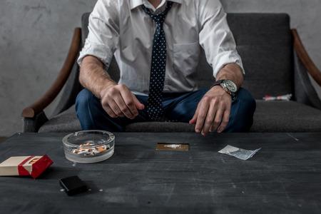 Captura recortada del empresario con adicción a las drogas preparándose para tomar cocaína
