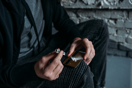 cropped shot of addicted junkie sniffing cocaine from credit card 스톡 콘텐츠