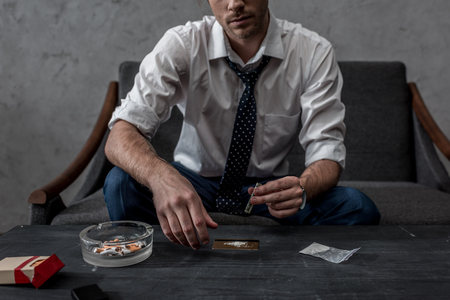 Captura recortada del joven empresario con adicción a las drogas preparándose para tomar cocaína