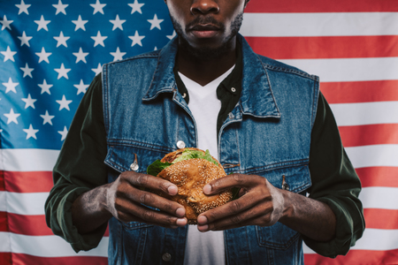 cropped shot of african american man holding burger against usa flag Stock Photo