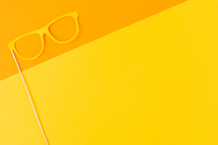 top view of masquerade mask on yellow and orange background