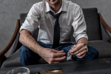 cropped shot of businessman with drug addiction holding pack of cocaine