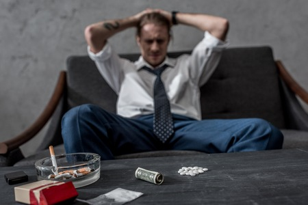 depressed businessman with drug addiction sitting on couch in front of table with mdma pills Stock Photo