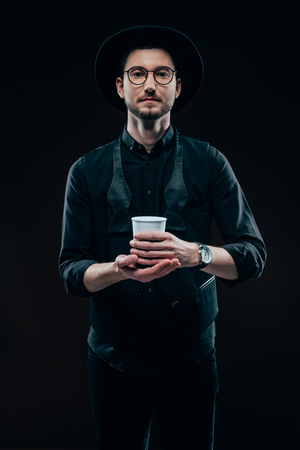 Man in black clothes holding coffee cup isolated on black