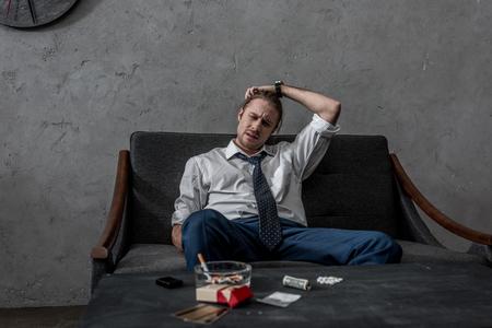 Hombre de negocios deprimido con adicción a las drogas sentado en el sofá frente a la mesa con drogas Foto de archivo