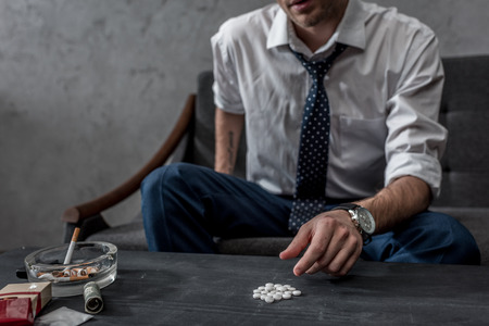 addicted junkie in white shirt and necktie taking mdma pill from table Stock Photo