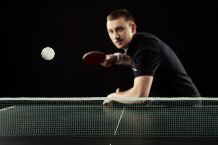 selective focus of young tennis player in uniform playing table tennis isolated on black Archivio Fotografico