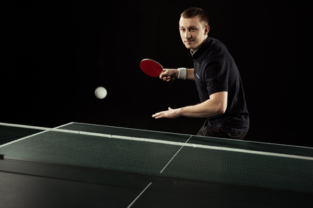 portrait of tennis player in uniform playing table tennis isolated on black Banque d'images - 111600888