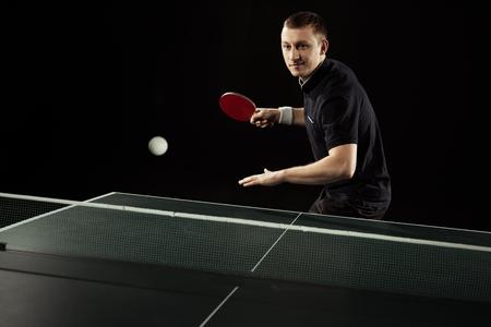 Ritratto di giocatore di tennis in uniforme giocando a ping pong isolato su black Archivio Fotografico