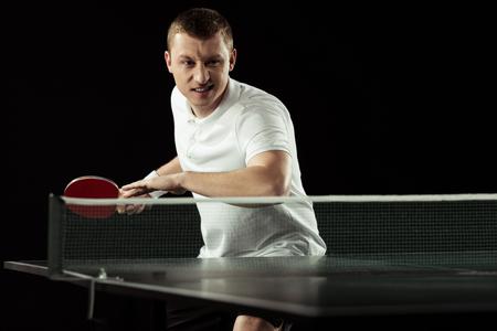 giovane giocatore di tennis emotivo in uniforme che si esercita nel tennis da tavolo isolato su nero
