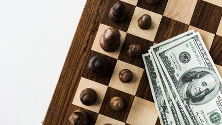 Cropped image of chessboard with cash and black chess pieces on white surface