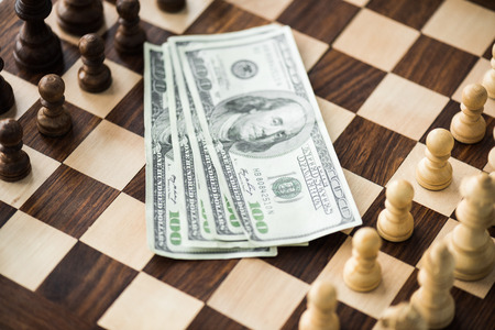 Close up view of dollar banknotes on chess board with set figures