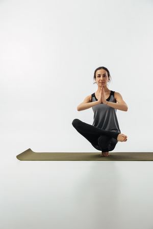 girl practicing toe stand on yoga mat on white
