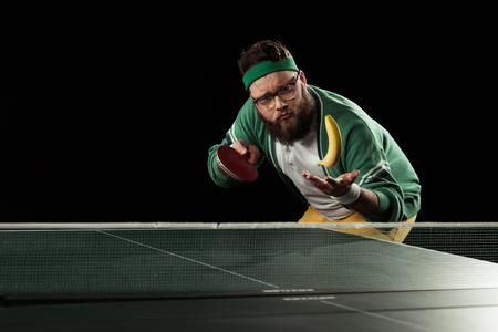 tennis player throwing up banana at tennis table isolated on black