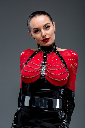 Seductive young woman in leather costume isolated on grey Banque d'images