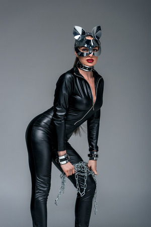 Seductive young woman wearing cat suit and mask holding chain isolated on grey