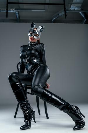 Kinky Frau im Kostüm posiert auf Stuhl auf grauem Hintergrund