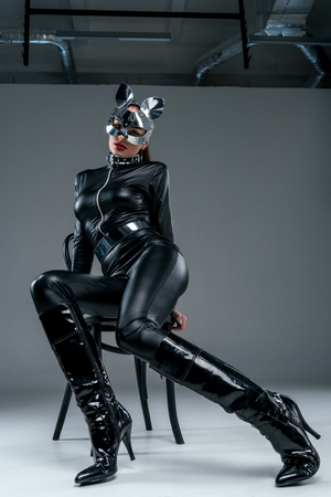 Kinky woman in costume posing on chair on grey background