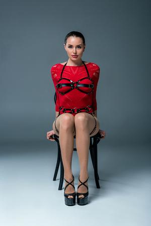 Séduisante jeune femme posant sur une chaise sur fond gris Banque d'images