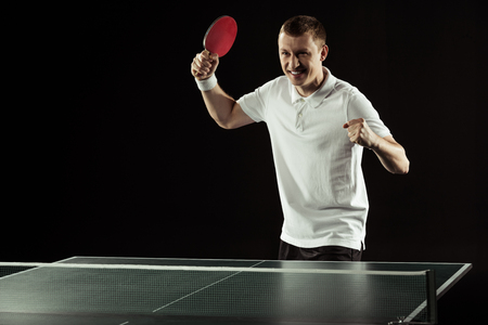 portrait of happy tennis player with tennis racket during game isolated on black Banque d'images