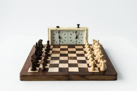 Reloj de ajedrez y tablero con piezas de ajedrez aislado en blanco